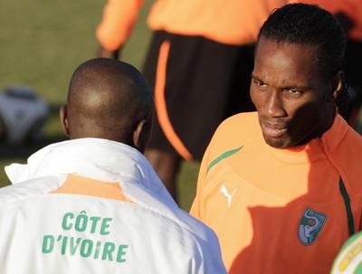Didier Drogba habla con uno de los miembros del cuerpo técnico de la selección