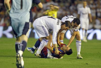 Uno de los momentos más polémicos: Arbeloa y Sergio Ramos levantan del suelo a Villa, que se lamenta tendido en el césped.