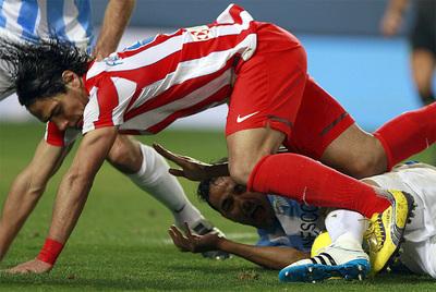 El delantero del Atlético, Radamel Falcao, cae ante el defensa Weligton.