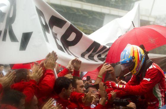 Alonso saluda a sus mecánicos al concluir la carrera.