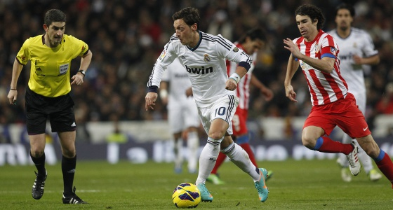Özil conduce el balón seguido por Tiago observado por Mallenco.