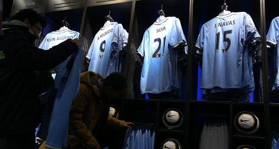 Dos aficionados observan las camisetas del Manchester City en la tienda oficial del club.
