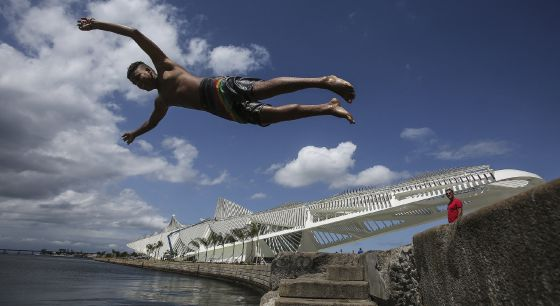 A young man dives into the water in Plaza Mauá