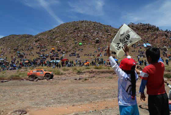 Dos niños bolivianos agitan una bandera del Dakar