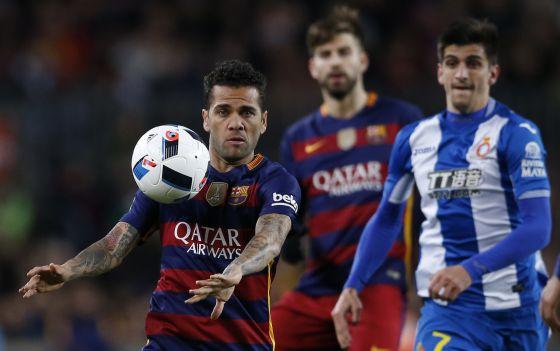 Alves controla el balón ante la mirada de Moreno y Piqué