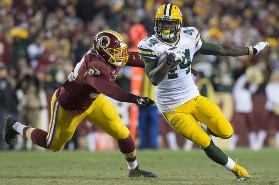 El running back de los Green Bay Packers James Starks escapa con el balón ante Preston Smith de los Redskins.