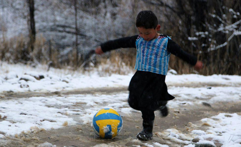 Murtaza, jugando en la nieve con la camiseta de plástico.