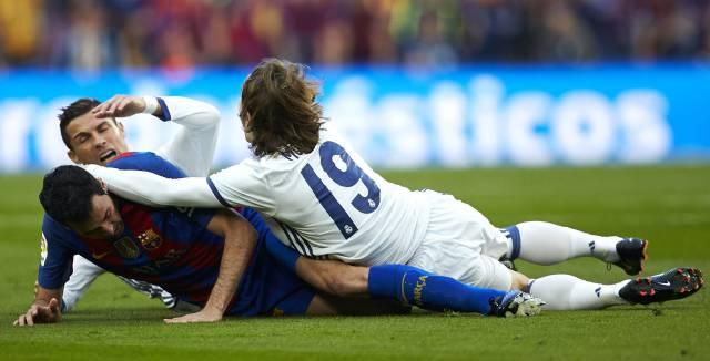 Modric, en el suelo junto a Busquets y Cristiano Ronaldo.