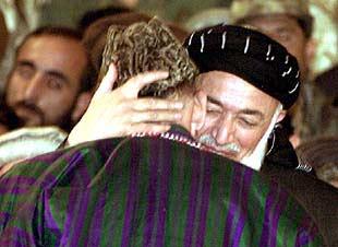 Karzai (de espaldas) recibe el abrazo del ex presidente Rabbani.
