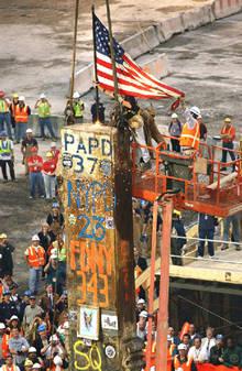Una bandera de EE UU es colocada sobre un pilar de las Torres Gemelas, en la  zona cero  de Nueva York, durante la conclusión de los trabajos de desescombro.