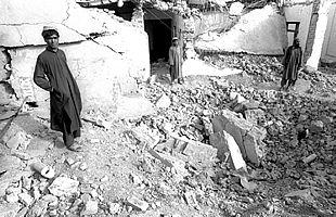 Varios vigilantes, entre las ruinas de la casa del clérigo Omar, que Estados Unidos bombardeó el pasado octubre.