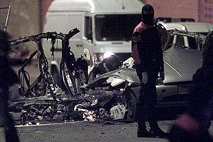 Un agente de la Ertzaintza, ante los restos del coche destrozado tras la explosión en Bilbao. PLANO GENERAL