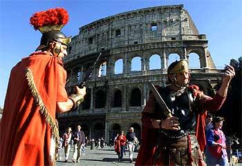 Dos hombres vestidos al estilo de los soldados romanos, ante el Coliseo.