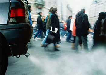 Peatones junto a un vehículo que emite gran cantidad de humo y sustancias contaminantes.