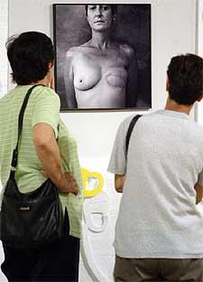 Dos mujeres visitan una exposición de fotos de mujeres con los pechos amputados por cáncer de mama.