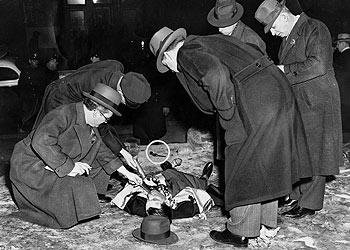 La policía examina el cadáver de Louis Cohen, asesino de Kid Dropper. Fotografía del  Daily News  de Nueva York, publicada en 1939, en la exposición del Museo Judío de Viena.