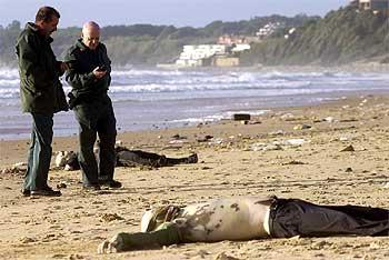 Dos guardias civiles, en una playa de Rota junto al cuerpo de uno de los inmigrantes fallecidos.