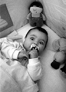 Un bebé en su cuna listo para dormirse solo.
