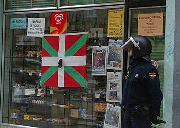 Un policía custodia la tienda donde ocurrió el tiroteo ayer en Pamplona.
