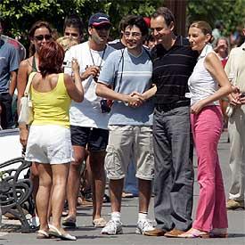 El presidente del Gobierno, acompañado por su esposa, Sonsoles, posan junto a un simpatizante en el puerto de Mahón.
