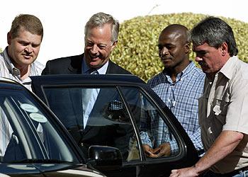 Mark Thatcher, de traje, sonríe al entrar en el coche tras ser detenido por la policía surafricana en Ciudad del Cabo.