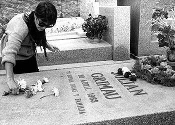 Una mujer pone flores en la tumba de Grimau (en la foto de abajo).