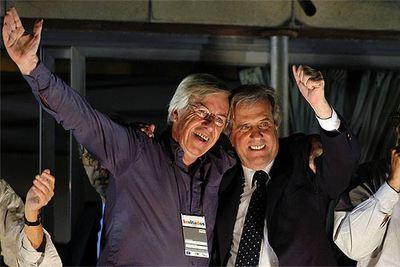 Tabaré Vázquez (a la derecha) saluda a sus partidarios abrazado al futuro ministro de Economía, Danilo Astori.