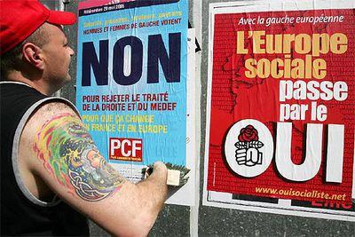 Un hombre pega un cartel del Partido Comunista a favor del  no  junto a uno socialista a favor del  sí.