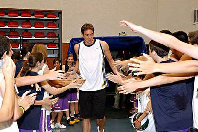 El jugador de baloncesto Pau Gasol saluda a niños en la localidad de Tres Cantos.