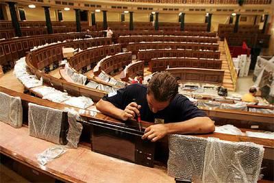 Un técnico trabaja en la instalación de monitores en los escaños del Congreso de los Diputados.