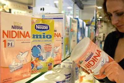 Una cliente de un supermercado de Santander muestra leches infantiles de Nestlé.