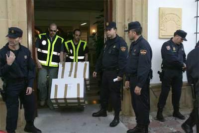 Dos policías sacan cajas con documentación de la sede del Ayuntamiento de Marbella.