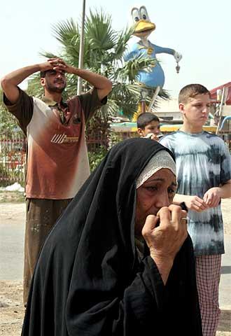Un grupo de iraquíes observa los efectos de una explosión en Bagdad que afectó a un autobús urbano el pasado domingo.