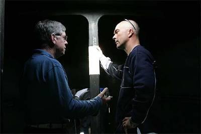 El ingeniero Bowler, a la izquierda, se dirige al patrón, Bekking, durante la reparación del barco en Portugal.