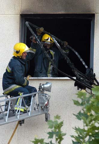 Dos bomberos en una ventana del piso siniestrado en for Compartir piso ciudad real
