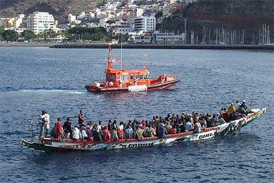 Una gran piragua con 103 ocupantes llega al puerto de San Sebastián de la Gomera escoltada por un barco de Salvamento Marítimo.