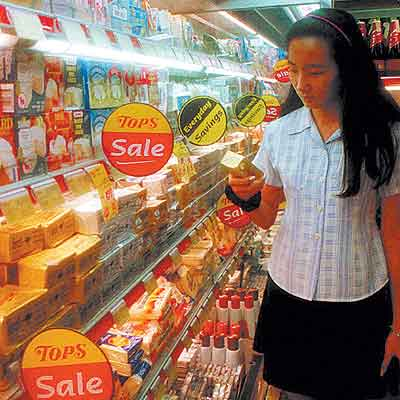 Una mujer mira las estanterías de mantequilla y lácteos en un supermercado de Bangkok.