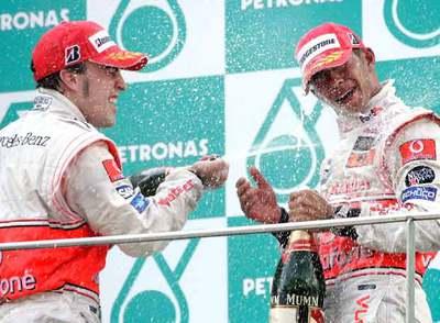 Alonso festeja con cava el triunfo junto a su compañero Hamilton.