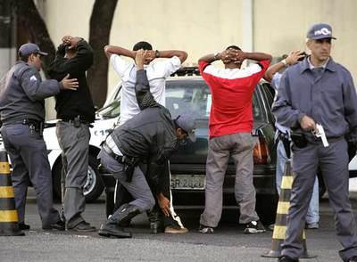 Varios policías cachean a cuatro hombres en São Paulo.