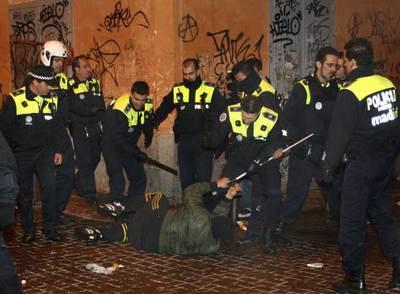 Un grupo de policías municipales rodea a un joven caído en el suelo, al que intenta quitar una muleta, en la confluencia de la calle de la Palma y Corredera Alta de San Pablo.
