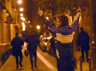 Un joven hace gestos obscenos a tres antidisturbios, de espaldas, en las proximidades de la plaza del Dos de Mayo la noche del miércoles.