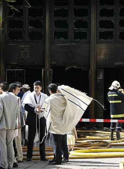 Varios judíos, ante la sinagoga destruida por el fuego en Ginebra.