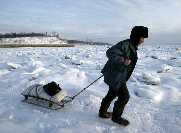 Un residente de Jabárovsk cruza el río Amur, completamente helado, arrastrando un pequeño trineo, en diciembre de 2004.
