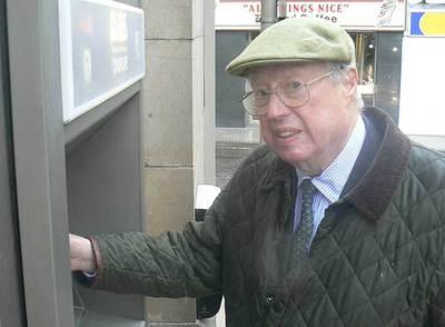 John Shepherd-Barron, el inventor del cajero automático, regocijándose ante su propia obra.