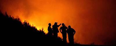 Bomberos y residentes de la villa de Kukurecani, en Macedonia, observan un incendio forestal.