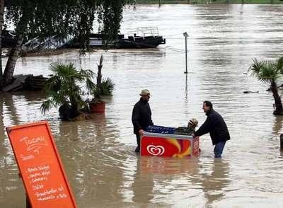 Unos vecinos rescatan cajas de cerveza en la orilla alemana del Rin, frente a la ciudad francesa de Estrasburgo.