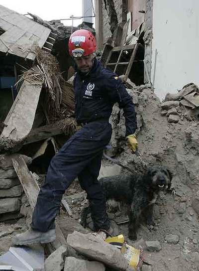 Un bombero español, con su perro de rescate ayer en Pisco.