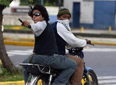 Un joven apunta con una pistola en medio de los disturbios entre estudiantes opositores y chavistas.