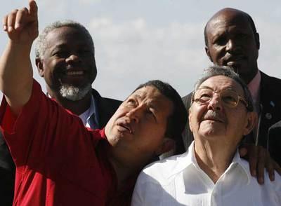 El presidente venezolano, Hugo Chávez, apunta al cielo y abraza al presidente de Cuba en funciones, Raúl Castro, en la cumbre Petrocaribe.