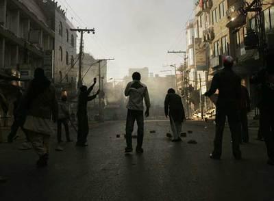 Seguidores de Benazir Bhutto tiran piedras a la policía en Rawalpindi, donde la ex primera ministra fue asesinada el jueves pasado.